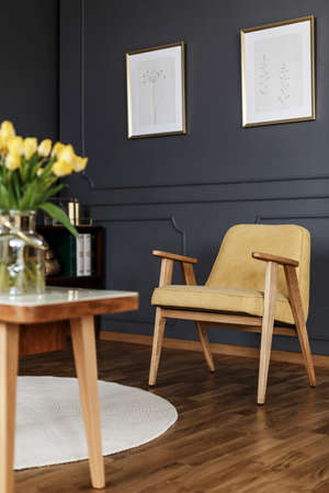 Real photo of a vintage living room interior with tulips on a wooden table in blurred foreground and a yellow armchair against dark wall with molding