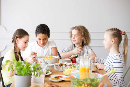 Group of children eating healthy dinner at friend's home Archivio Fotografico - 104667554