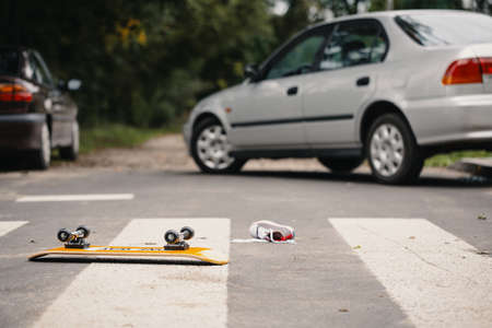Skateboard and childs shoe on a pedestrian crossing after dangerous traffic incident Stock Photo