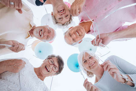 Low angle of happy senior people in the circle with balloons during party 版權商用圖片 - 104667557
