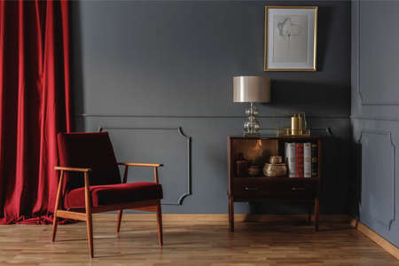 Real photo of a corner of a retro living room interior with elegant, beige lamp on a wooden cabinet next to a red armchair Stock Photo