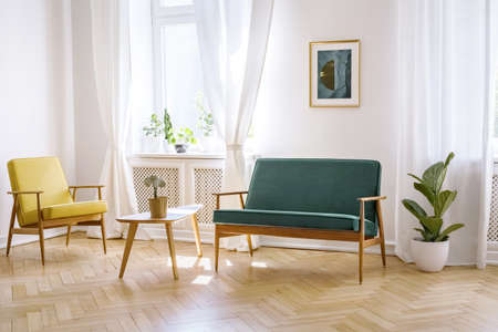 Wooden table between yellow armchair and green bench in white flat interior with poster. Real photo