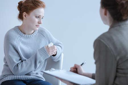 Chica triste sosteniendo un pañuelo y hablando con su terapeuta durante una reunión
