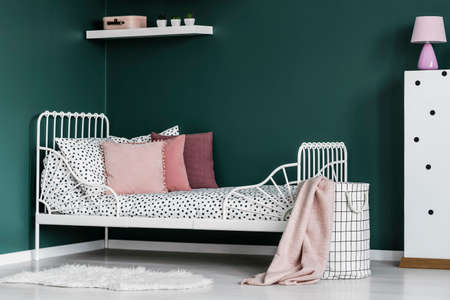 Pink pillow on white bed in green girls room interior with lamp on cabinet Stock Photo