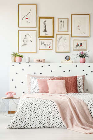 Pink blanket on patterned bed with headboard in womans bedroom interior with posters