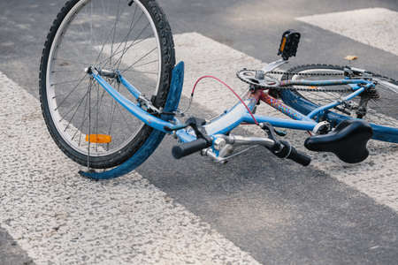 Blue child's bicycle lying on a pedestrian crossing after a traffic accident