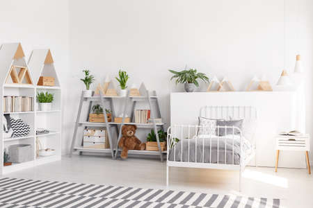 Plants and plush toy on shelves in scandi child's bedroom interior with grey sheets on bed. Real photo