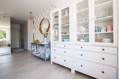 White kitchen cupboard with pastel dishes and blue console table standing in real photo house interior with patterned wallpaper and mirror on the wall