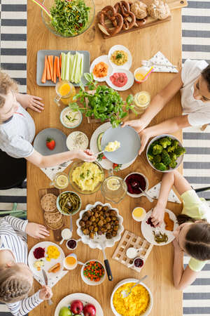 Top view on children eating healthy food during friends birthday