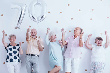 Smiling senior people celebrating with silver balloons during birthday party Stok Fotoğraf