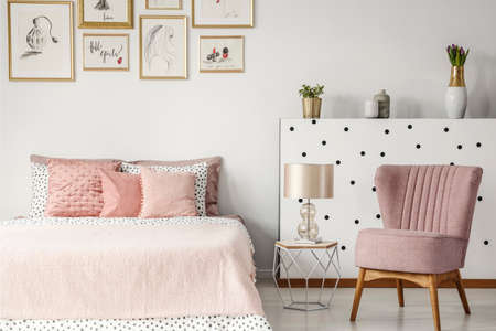 Pink armchair next to table with lamp and bed in pastel bedroom interior with posters