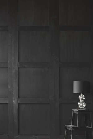 Lamp on stool against wooden wall in empty dark black interior with copy space. Real photo