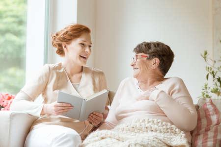 Glückliche Krankenschwester, die ihrem älteren Patienten in einem privaten Pflegeheim ein lustiges Buch vorliest