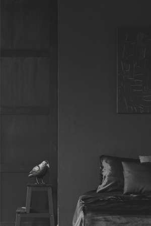 Sculpture on stool next to bed in black bedroom interior with decor on the wall. Real photo Stock Photo