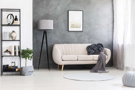 Poster mock-up on a gray, concrete wall and a leather beige settee in an industrial living room interior with black, wooden furniture Stok Fotoğraf - 105282732