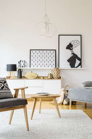 Real photo of an armchair standing in living room interior next to a small table on a white rug with shelf with posters and cupboard with ornaments in the background Фото со стока