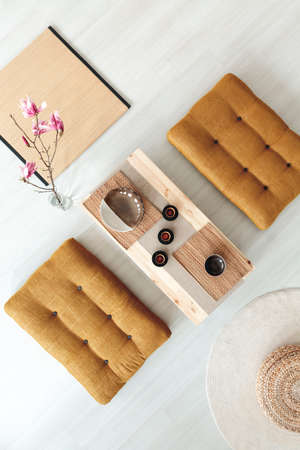 Top view on wooden table with cups between poufs in dining room interior with flowers. Real photo