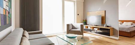 Televisión en mueble de madera en el interior de la sala de estar con sillón junto a la ventana. Foto real Foto de archivo
