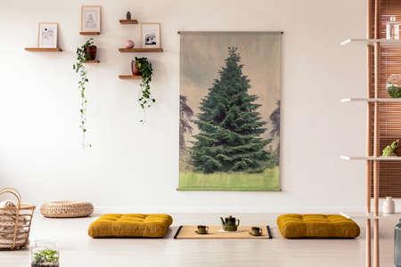 Gelbe Hocker auf dem Boden im Innenraum des japanischen Esszimmers mit Tatami-Matte und Plakat. Echtes Foto Standard-Bild