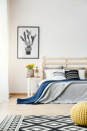 Black and white cactus poster hanging on the wall in bright bedroom interior with yellow fresh flowers, double bed and patterned carpet Banco de Imagens