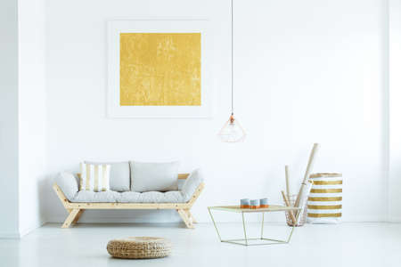 Real photo of a couch with a stripped cushion standing next to a table and baskets in white living room interior with a painting on a wall Banco de Imagens