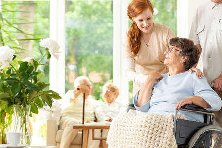 Cuidador tierno despidiéndose de un jubilado anciano en silla de ruedas en una guardería. Un compañero empujando la silla de ruedas. Otras personas mayores en el fondo borroso.