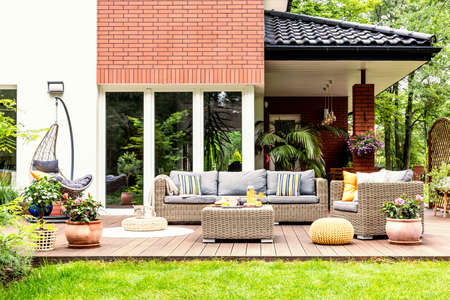 Real photo of a beautiful terrace with garden furniture, plants and swing