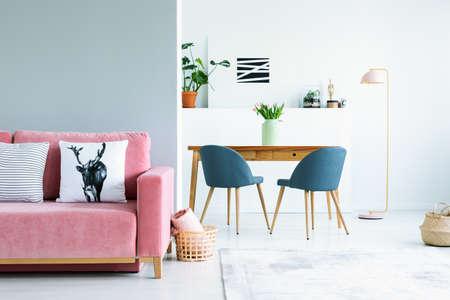 Foto real de un interior plano de espacio abierto con un sofá rosa en la sala de estar y una mesa de madera con sillas grises en el comedor.