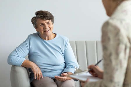 Smiling senior woman talking to a psychologist about happy life of a pensioner