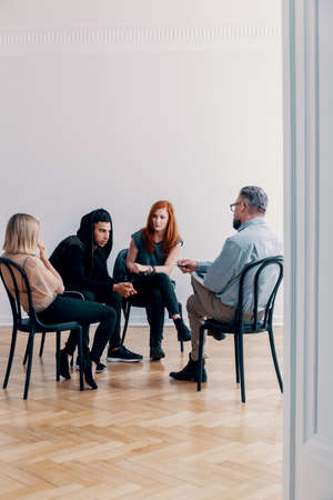 Group of rebellious teenagers talking to a psychologist in a rehab facility Stock Photo