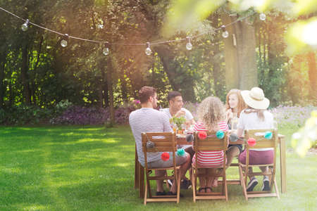 Multicultural group of friends eating lunch in the garden on a sunny day Stockfoto