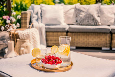 Fruits and glass with water on rattan table on the terrace with settee and flowers. Real photo with blurred background Stock Photo