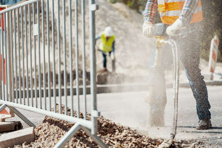 Close-up of a pneumatic hammer held by a worker and dust in the air at roadworks