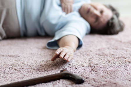 Close-up of grandmother with heart attack trying to reach her cane lying on the floor