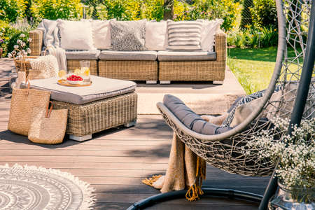 Pillows on rattan couch and table on patio with hanging chair during summer. Real photo Stock Photo
