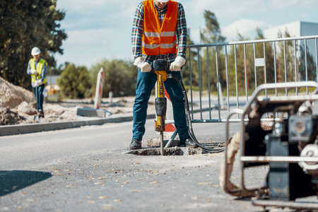 Worker with a pneumatic hammer breaking asphalt at road construction site