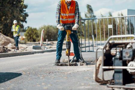 Trabajador con un martillo neumático rompiendo el asfalto en el sitio de construcción de carreteras Foto de archivo