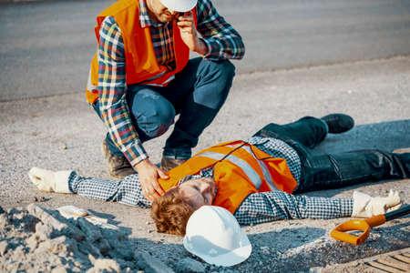 Uomo preoccupato che chiama un'ambulanza per il suo collega privo di sensi