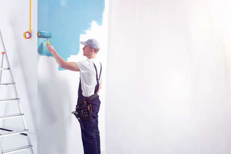 Decorator wearing overalls painting a room blue. Place your graphic on the empty wall