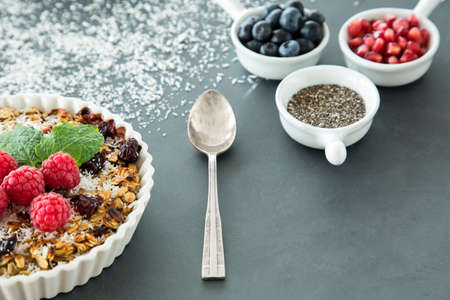 Spoon between dessert with raspberries, linseed, pomegranate seeds and berries Stockfoto
