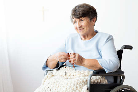Paralyzed senior woman in a wheelchair praying to god using rosary Stock Photo