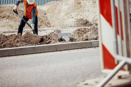 Low angle of a construction worker digging a hole in the road Stock Photo