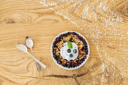 Top view of muesli with berries and cream on wooden table with spoons. Stylish food