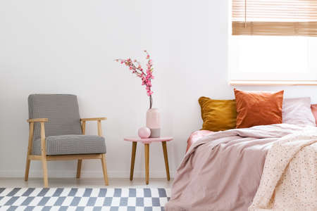 Flowers On Table Between Patterned Armchair And Pink Bed In Bedroom Simple Patterned Armchair