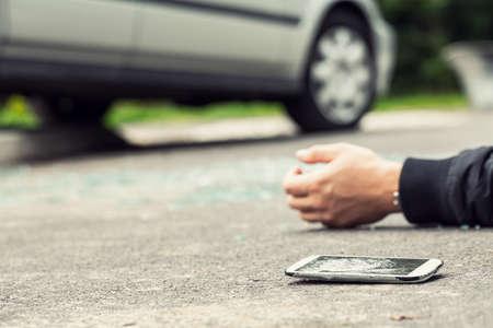 Broken phone next to a hand of a victim lying on the street Фото со стока