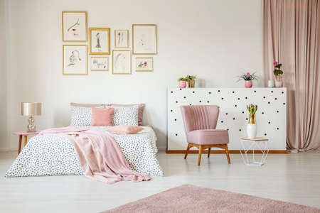 Pink armchair in spacious bedroom interior with blanket on bed against white wall with posters