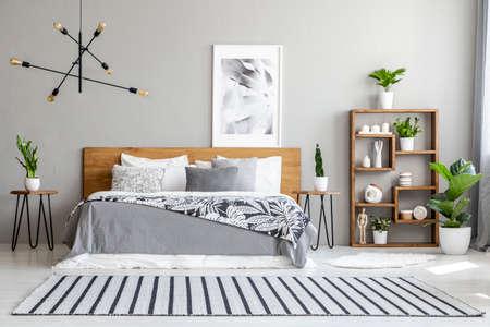 Tapis rayé près du lit avec couverture à motifs à l'intérieur de la chambre avec affiche et plantes. Vrai photo