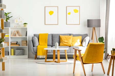 Żółty drewniany fotel i stół we wnętrzu salonu z plakatami nad szarą sofą. Prawdziwe zdjęcie