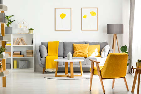 Gele houten fauteuil en tafel in woonkamer interieur met posters boven grijze bank. Echte foto