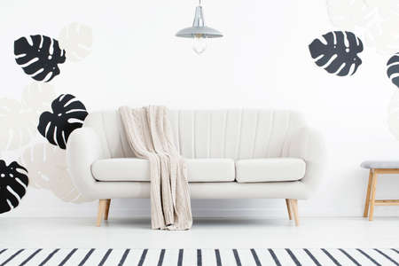 Lamp above couch with blanket in white living room interior with striped rug and leaves. Real photo Banco de Imagens